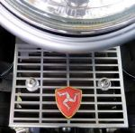 Triumph Rectifier Guard Isle Of Man Logo Shield. Bonneville Thruxton Scrambler. 2002/15. Matt Chrome.